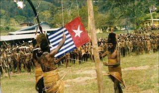 Morning Star flag being raised by Yali tribesman (supplied)